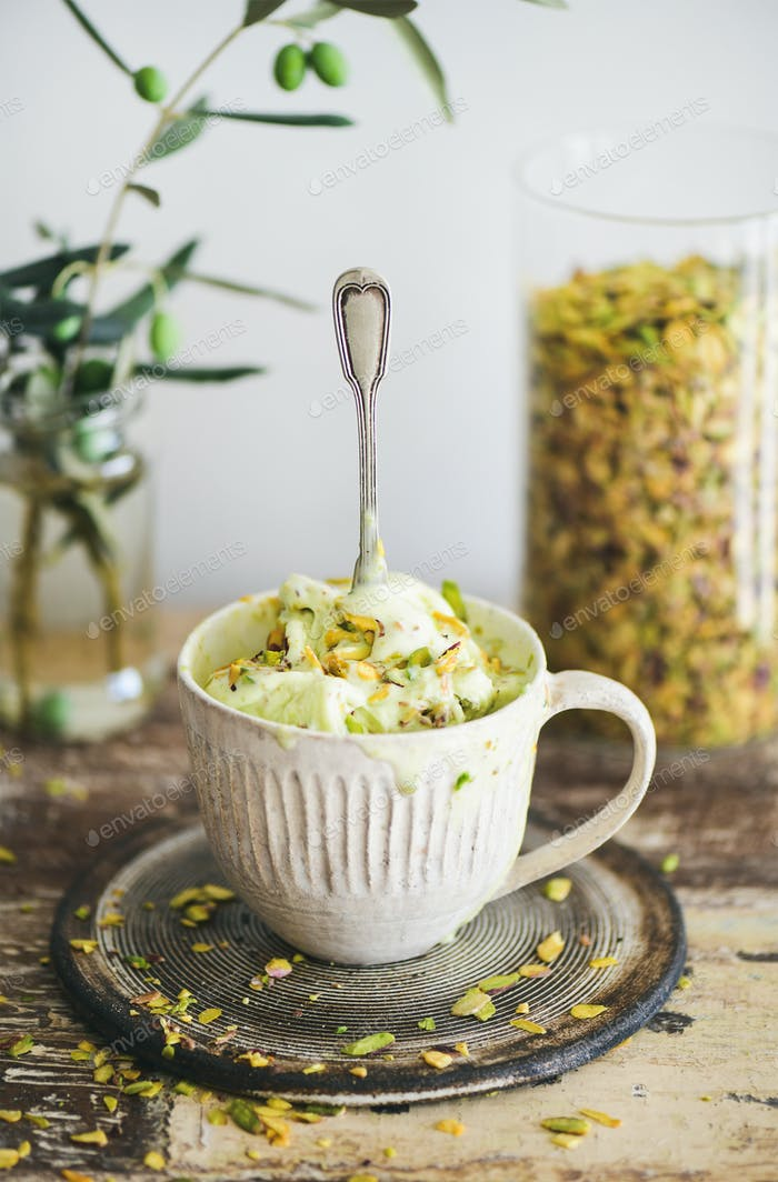 Pistachio ice cream in mug with pistachio nuts