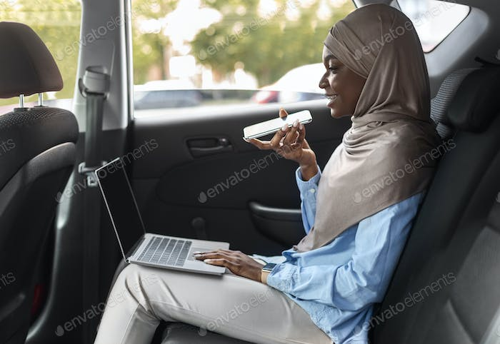 Black Muslim Woman Sending Voice Message And Using Laptop In Car