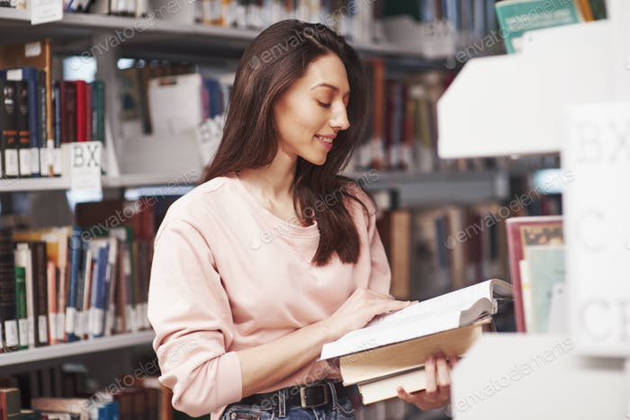 Quick read. Brunette girl in casual clothes having good time in the library full of books