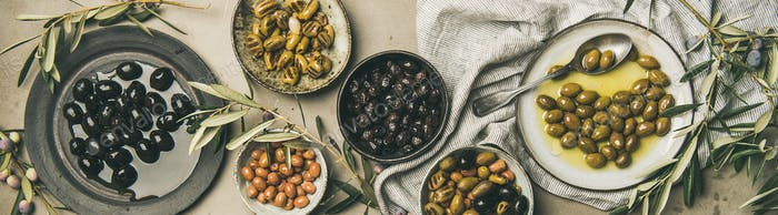 Mediterranean pickled olives and olive tree branches, wide composition