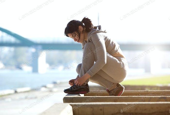 Young woman tying shoe lace before run