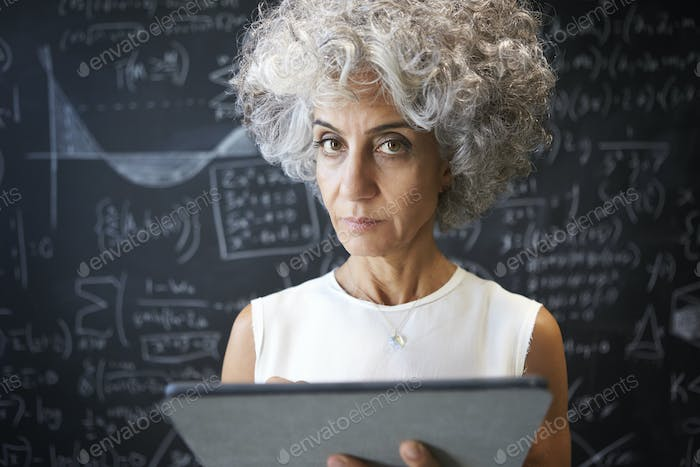 Middle aged academic woman using tablet looking to camera