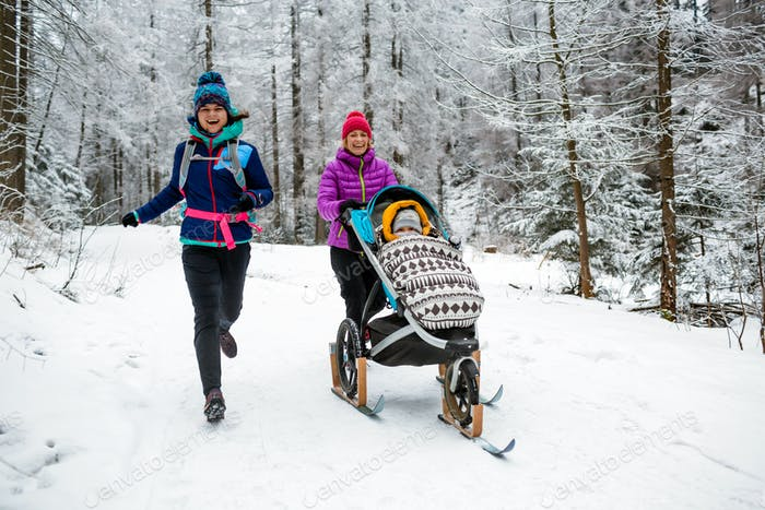 Mutter mit Kinderwagen genießen Winter im Wald, Familienzeit