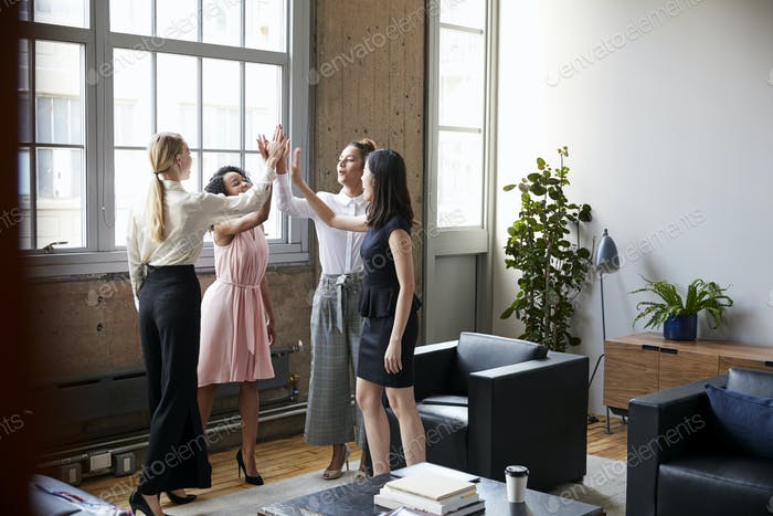 Female colleagues high five at a motivational meeting