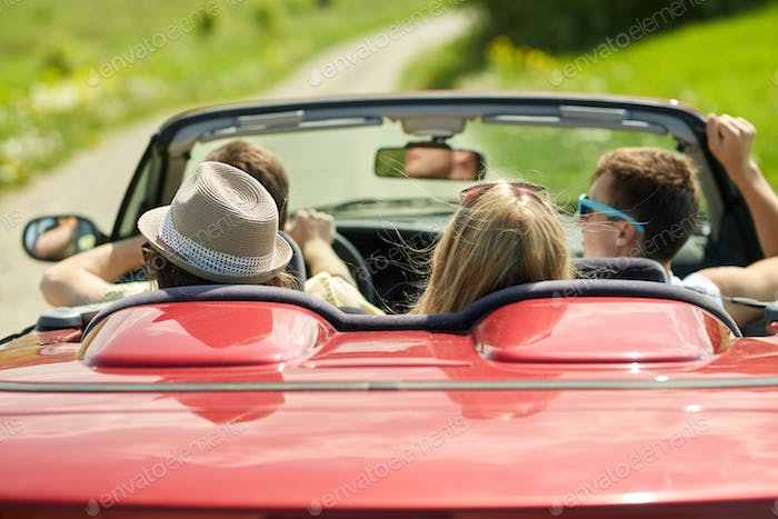 happy friends driving in convertible car at summer