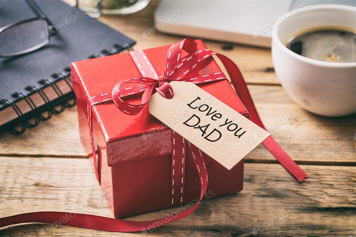 Father's day. Red gift box with love you dad tag, blur office desk background