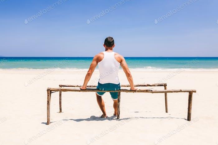 fitness-mann am strand rückansicht