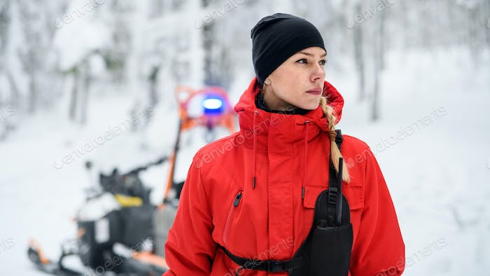 Woman paramedic from mountain rescue service outdoors in winter in forest.