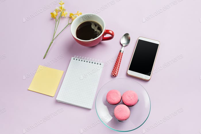 The top view on female desk. The phone and french macarons on trendy pink desk.