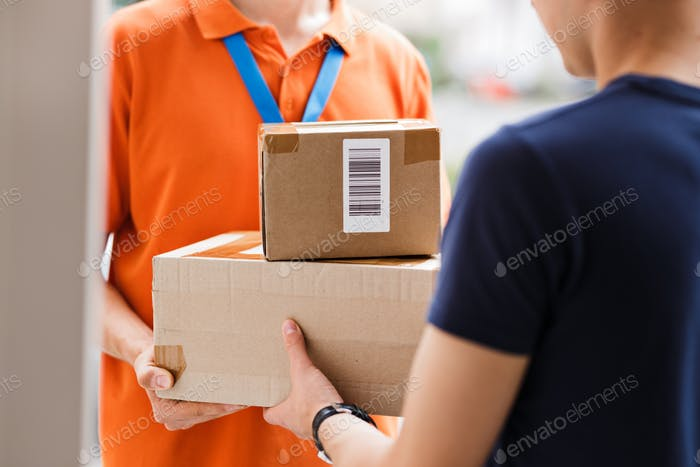 A person wearing an orange T-shirt and a name tag is delivering parcels to a client. Friendly worker