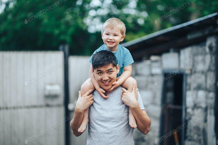 niño rubio de tres años sentado sobre los hombros de su padre. Padre kazajo y madre caucásica
