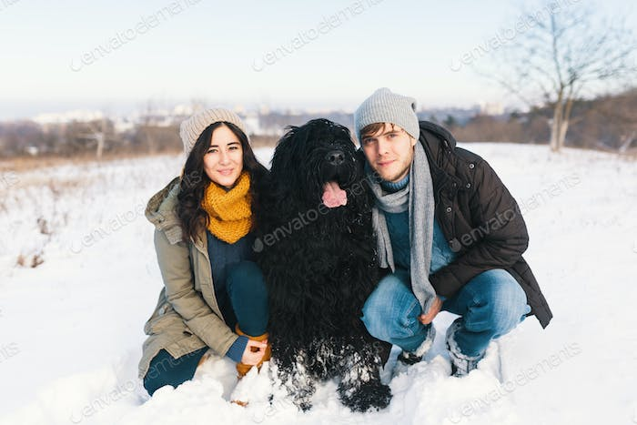 A couple enjoying winter while walking their big black dog havin