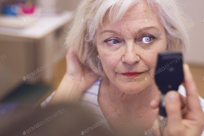 Senior woman having eyes checked by doctor
