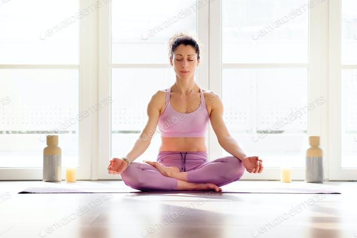 Woman meditating in half lotus pose