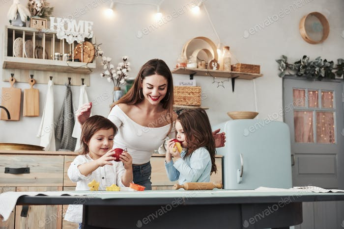 Young beautiful woman feeds two kids with apples while they sitting near the table with toys
