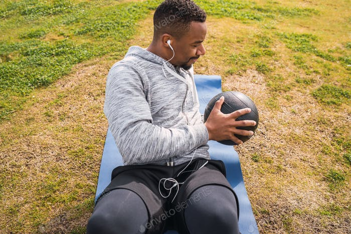 Athletic man doing exercise with medicine ball.