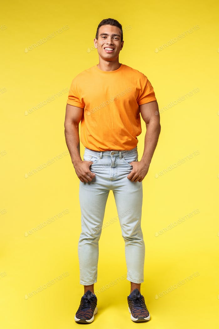 Vertical full-length studio shot young hipster guy with mascular body, standing orange t-shirt and