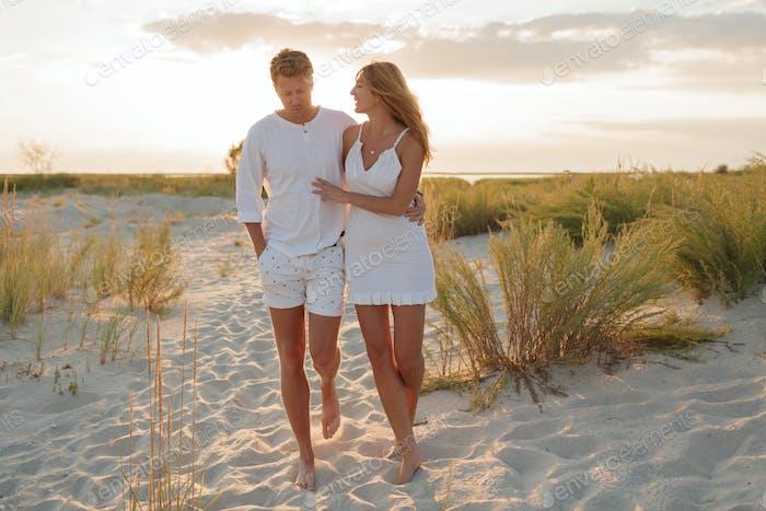 Beach couple walking barefoot on sand at sunset walk honeymoon.