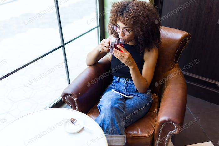 Beautiful young woman drinking red tea in a coffee shop.