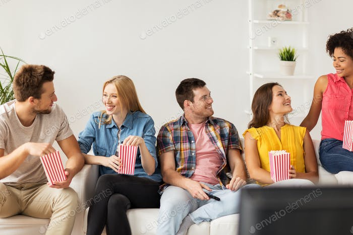 happy friends with popcorn and tv remote at home