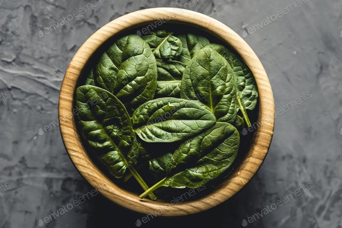 Baby spinach leaves in bowl on grey concrete backgroundClean eating, detox, diet food ingredient