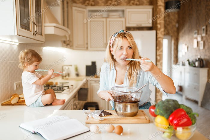 Mother and her daughter tastes melted chocolate