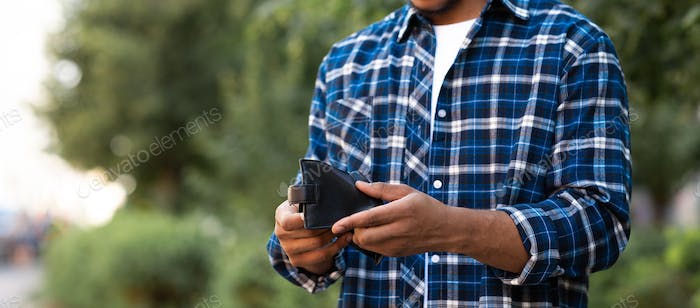 Cropped image of black guy looking at his empty purse