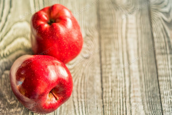 Red juice ripe apples on wooden background
