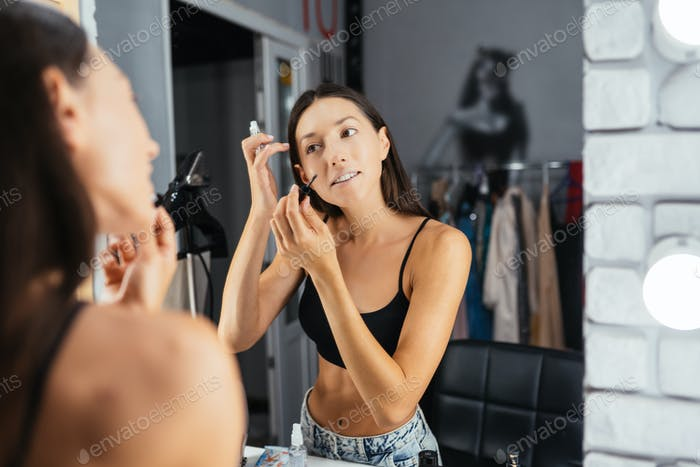 Reflection of young beautiful woman applying her make-up