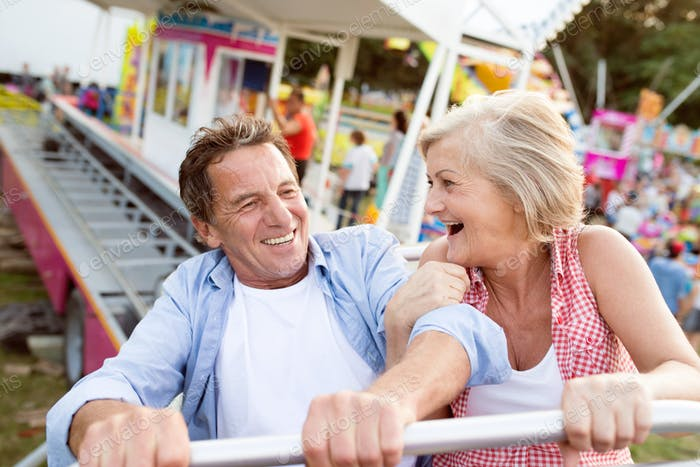 Senior couple on a ride in amusement park