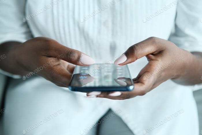 Black Woman Looking For Application On Smartphone