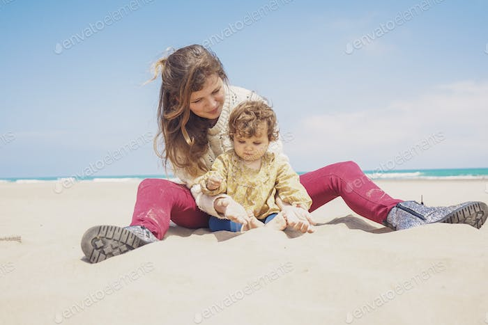 Young mom playing at the beach with her child