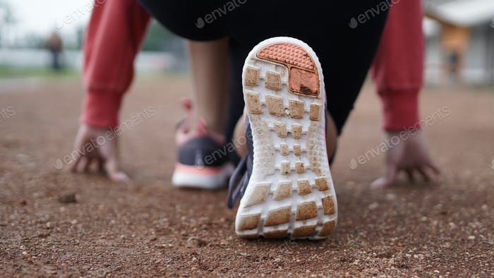 Close up shoes of woman athlete getting ready to start running on track