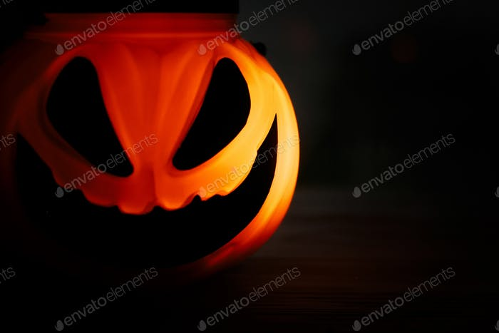 Halloween pumpkin Jack-o'-lantern with scary glowing face on black background