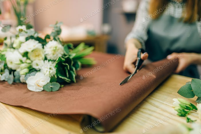 Female florist hands cuts decoration with scissors