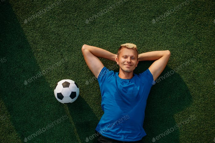 Male soccer player with ball lying on the grass