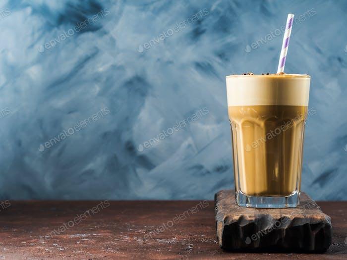 Frappe Kaffee im hohen Glas auf blau und braun