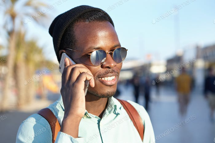 Cheerful trendy looking African American student in round sunglasses and headwear making phone call,