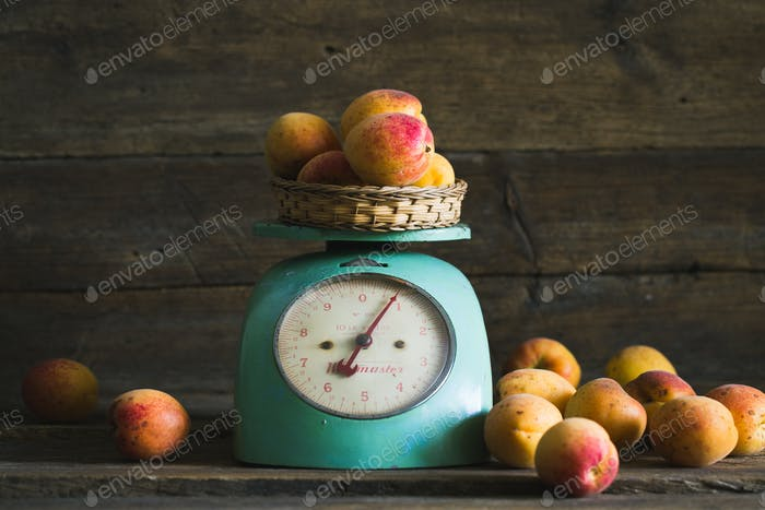 Apricots with kitchen scales on a wood background. toning. Vegetarian food. Healthy life.