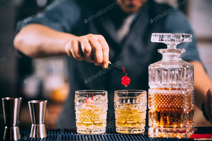 bartender preparing and lining crystal whisekey glasses for alcoholic drinks on bar