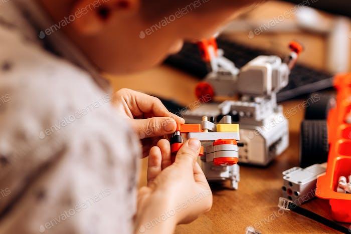 Smart Junge in grauem Hemd gekleidet macht einen Roboter aus dem Roboter-Konstruktor am Schreibtisch in der Schule