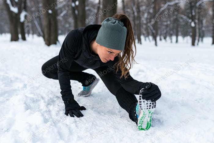 Female athlete exercising in park in winter