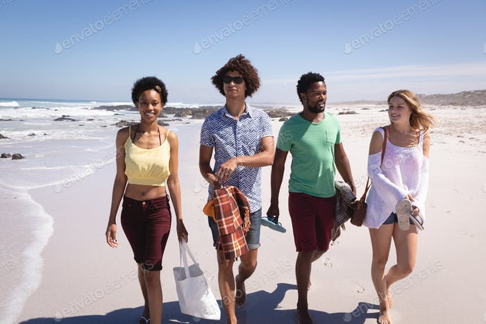 Group of friends walking side by side on the beach and smiling