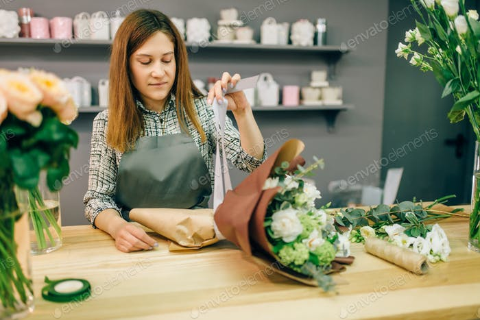 Florist attaches a bow to fresh flower composition