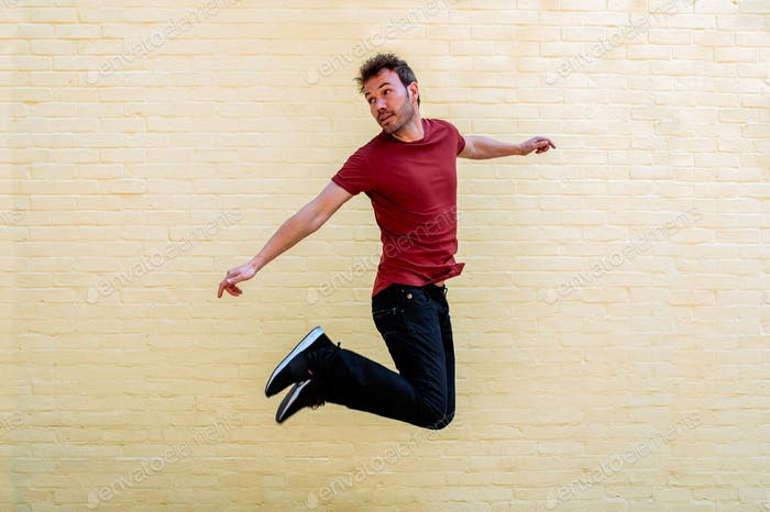 Happy man jumping by colorful wall in notting hill