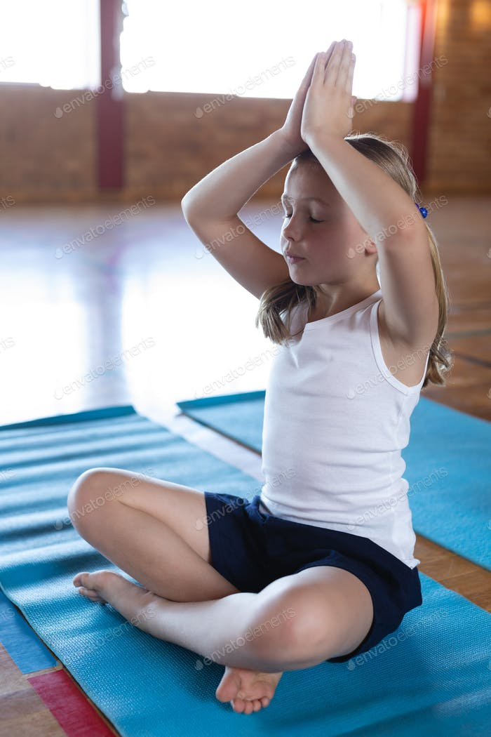 Side view of schoolgirl doing yoga and meditating on a yoga mat in school