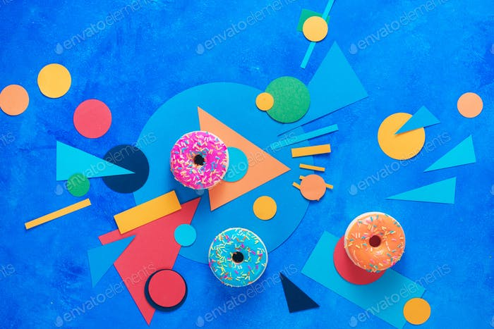 Donuts with colorful paper decorations. Color blocking flat lay header with sweets. Creative food