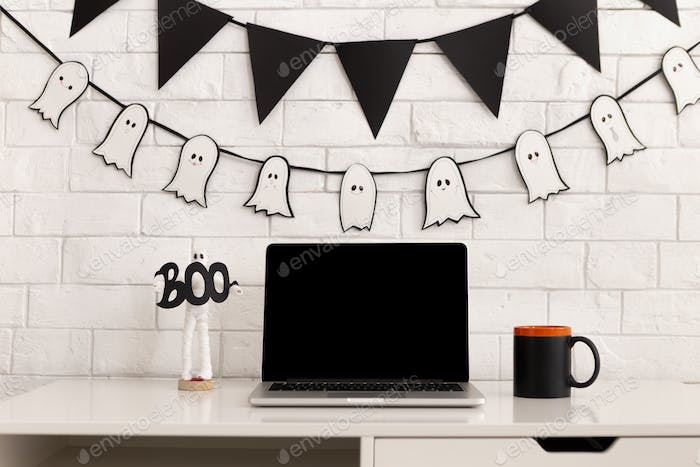 Workplace decorating for Halloween party with open laptop