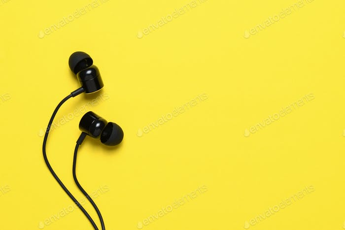 Earbuds on yellow background with text space