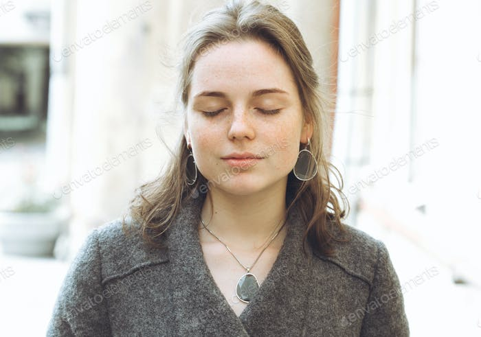 Beautiful woman face portrait freckles street city fashion nature. Girl in wool coat with jewelry.